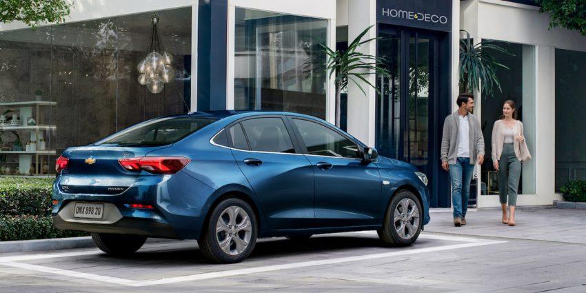 Chevrolet Onix Plus azul em frente a uma loja decoração com um casa indo até o carro
