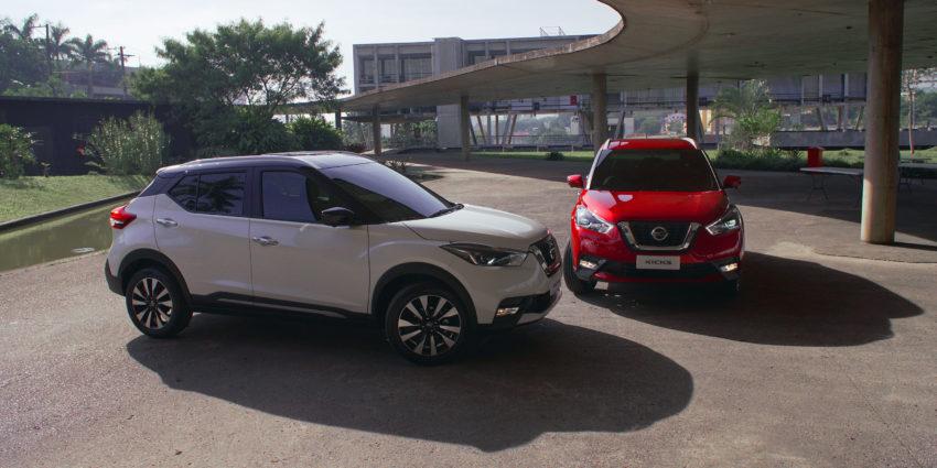 Nissan Kicks 2020 branco e vermelho lado a lado em pátio de um edíficio