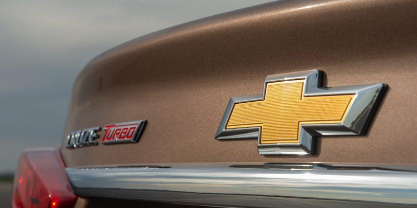Logo da Chevrolet em traseira de um Cruze bege